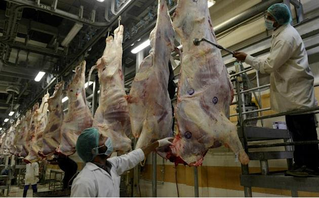 Health inspectors certify meat by placing stamps at a government slaughterhouse in Lahore
