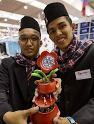 Hafizuddin Abdul Rahman (L) and Ahmand Syafiq Amirudin with their invention -- an electricity system using decomposing garden soil in place of batteries -- at the International Exhibition of Inventions in Geneva on April 10, 2013