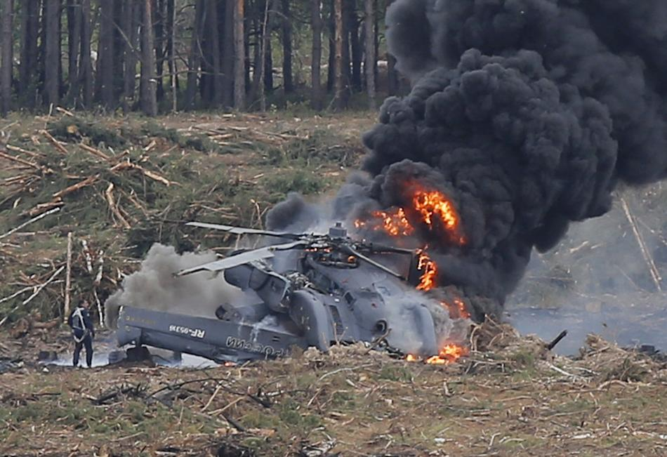 A pilot stands near a burning Mi-28N helicopter after a hard touchdown during the