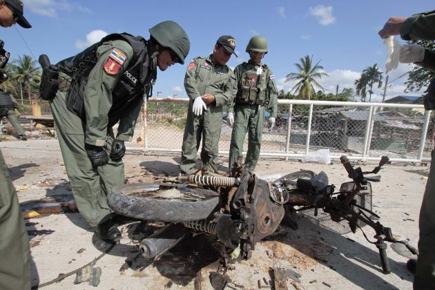 Police and forensic experts inspect the site of a motorcycle bomb attack in the troubled southern province of Narathiwat