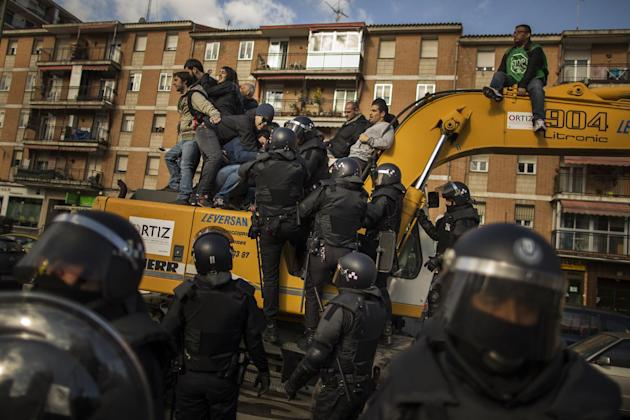 Riot Police remove a housing rights activists who claimed a bulldozer as they triy to stop Luisa Gracia Gonzalez and her family's eviction and the demolition of their house by a forced expropriati