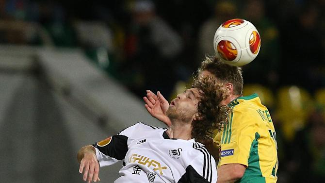 Swansea City's Jose Canas, left, jumps for a ball with Kuban Krasnodar's Vladislav Ignatyev, right, during their Europa League group A soccer match at a stadium in Krasnodar, Russia, Thursday, Nov. 7 2013