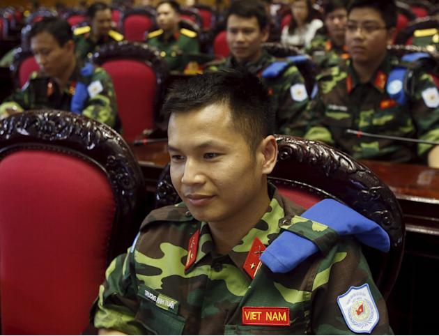 Soldiers of Vietnam's Peacekeeping Center listen as U.N. Secretary-General Ban Ki-moon speaks at the review conference on Vietnam's one-year participation in U.N. peacekeeping operations, at t