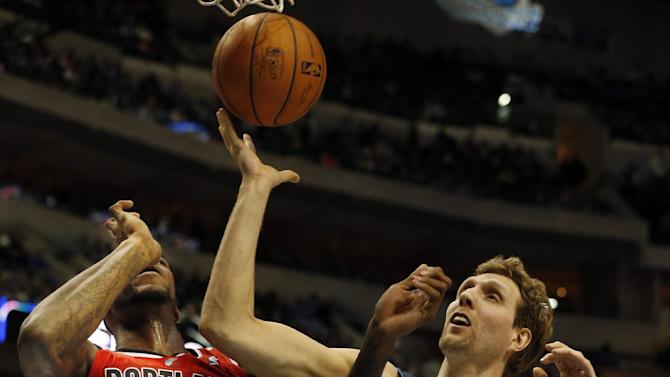 Portland Trail Blazers forward Thomas Robinson, left, and Dallas Mavericks forward Dirk Nowitzki, right, of Germany, fight for a loose ball during the first half of an NBA basketball game on Friday, March 7, 2014, in Dallas