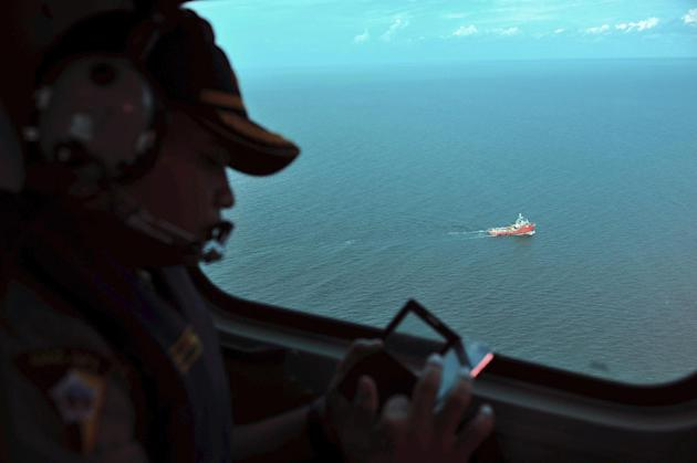 A crew member of an Indonesian Air Force Super Puma helicopter looks out of a window as rescue ship Crest Onyx transporting the tail part of the ill-fated AirAsia Flight 8501 is seen on the Java Sea, Sunday, Jan. 11, 2015. A day after the tail of the crashed AirAsia plane was fished out of the Java Sea, the search for the missing black boxes intensified Sunday with more pings heard. (AP Photo/Zulkarnain, Pool)