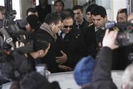 Baris Guler (C in sunglasses), son of Turkey's Interior Minister Muammer Guler, is escorted by plainclothes police officers as he leaves a medical check-up in Istanbul December 16, 2013. Turkish police detained the sons of three cabinet ministers and several well-known businessmen as part of investigations into alleged corruption on Tuesday, state officials said, in a blow to Prime Minister Tayyip Erdogan months ahead of elections. REUTERS/Kursat Bayhan/Zaman Daily via Cihan News Agency