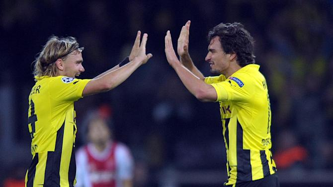 In this Sept. 18, 2012 fiile picture Dortmunds Marcel Schmelzer , left, and Mats Hummels celebrate after winning the UEFA Champions League group D soccer match Borussia Dortmund vs. Ajax Amsterdam at  in Dortmund, Germany. Borussia Dortmund has lost two more defenders to injuries in a major blow before its Bundesliga showdown with Bayern Munich.  Mats Hummels and Marcel Schmelzer both have been ruled out of Saturday's match, meaning that three of Dortmund's regular defenders won't be available. Neven Subotic is out for the season with a knee injury. Hummels, a central defender, twisted his right foot and damaged ligaments in his heel in Germany's 1-0 win over England on Tuesday Nov. 19, 2013 . Schmelzer sustained a right-calf injury in the same game