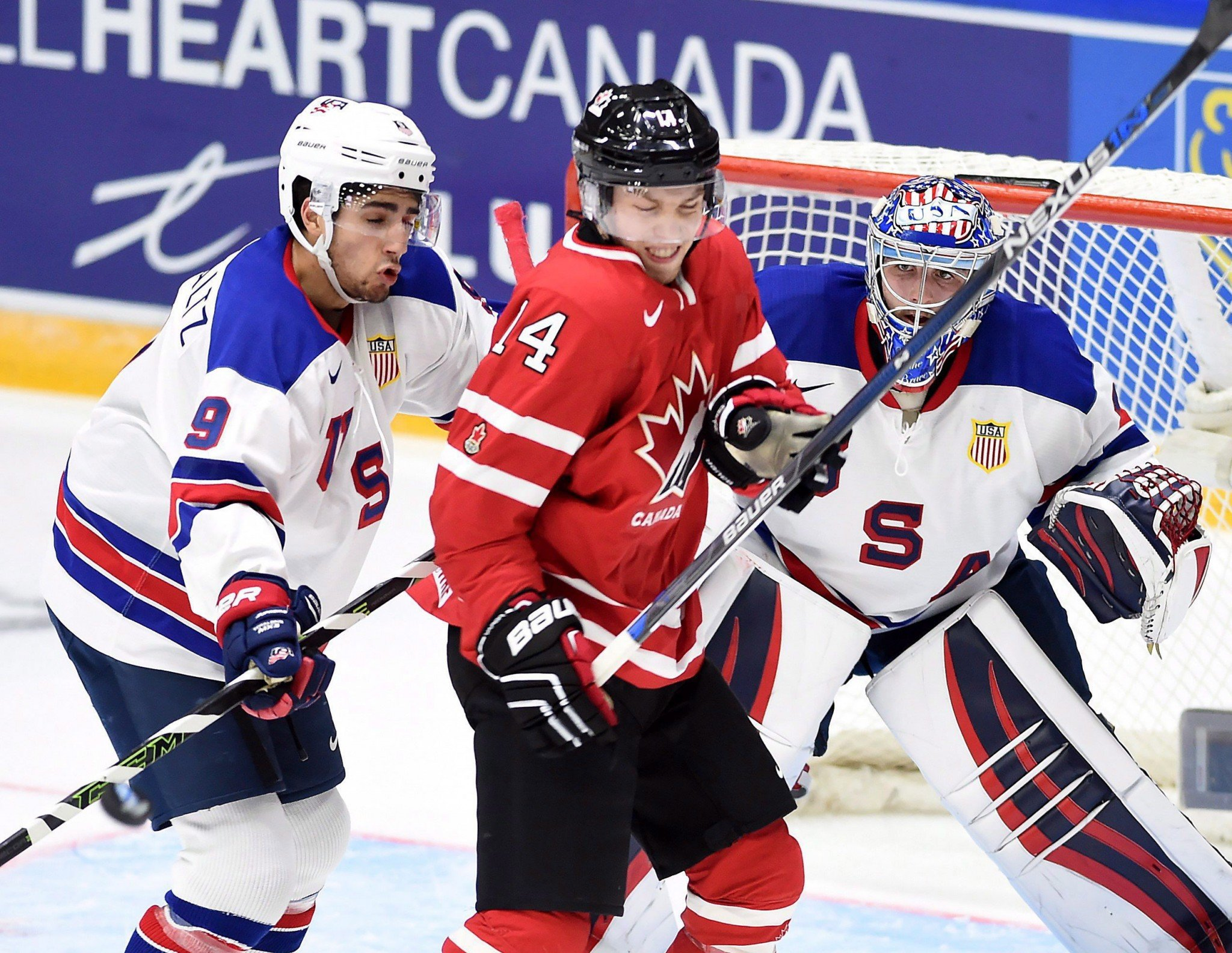 Canada's Rourke Chartier (14) takes a shot from a teammate as the United States' Nick Schmaltz (9) tries to check him away from the crease during the 2016 world junior championship in Helsinki, Finland. (THE CANADIAN PRESS)