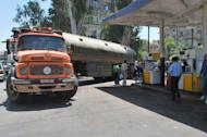 A tanker arrives at a petrol station as Syrians wait for fuel in Damascus. Feared forces led by President Bashar al-Assad's brother used helicopter gunships Sunday in a new assault on rebels in Damascus, activists said, as clashes also raged in Syria's second city Aleppo