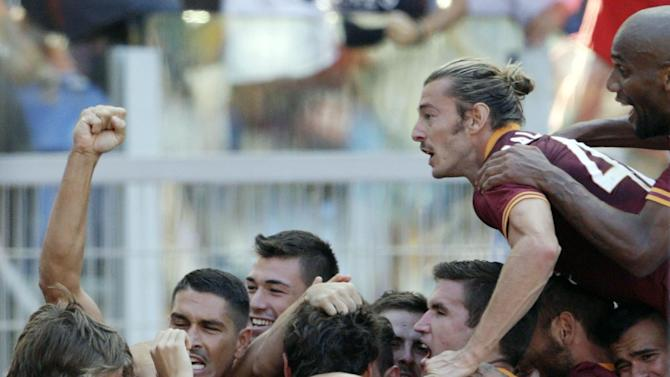 AS Roma players celebrate after their teammate forward Adem Ljajic of Serbia, back to camera, scored during a Serie A soccer match between As Roma and Lazio, in Rome's Olympic stadium, Sunday, Sept. 22, 2013