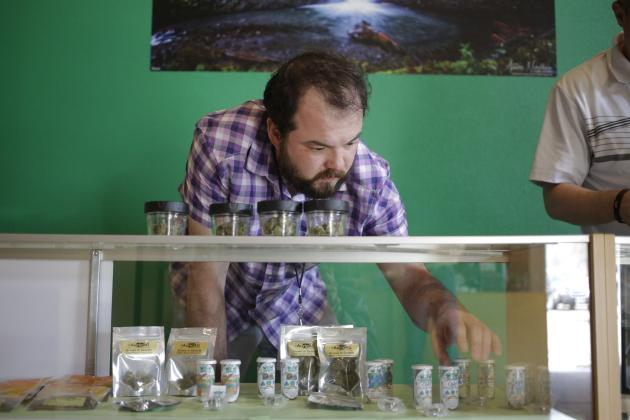"""""""Bud tender"""" Huntington stocks up a display case with products at The Cannabis Corner in North Bonneville"""