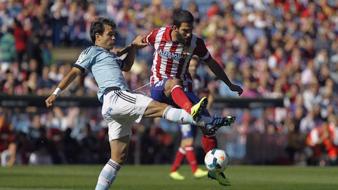 Atletico de Madrid's Arda Turan from Turkey, right, in action with Celta de Vigo's Borja Oubina, left, during a Spanish La Liga soccer match at the Vicente Calderon stadium in Madrid, Spain, Sunday, Oct. 6, 2013