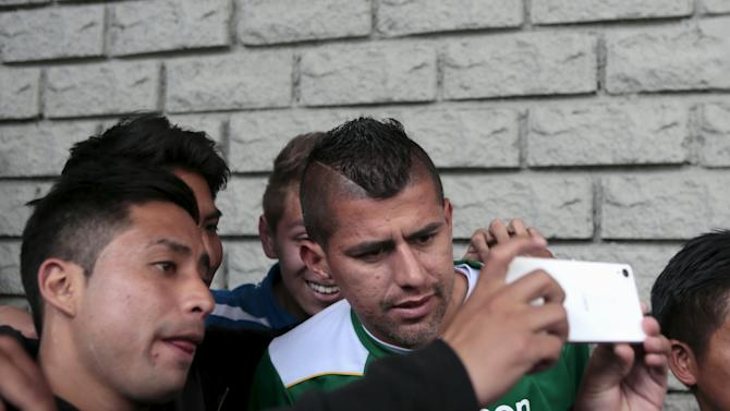 Supporters take a selfie with Arce of Bolivia's national soccer team before a training session in La Paz