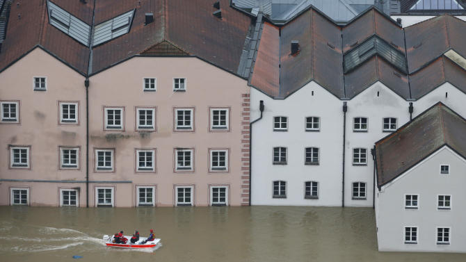 FILE - In this June 3, 2013 file picture members of the Red Cross make their way by boat in a flooded street in the center of Passau, southern Germany. A leading insurance company says flooding in central Europe last month caused damage totaling more than US $16 billion, about a quarter of it insured — making it the year's costliest natural disaster so far. Munich Re AG put insured losses from the flooding in Germany and several other countries at US $3.9 billion. Both figures were similar to the damage caused by floods in 2002 that hit some of the same areas. Munich Re said Tuesday July 9, 2013 that overall losses caused by natural disasters totaled a below-average US $45 billion between January and June, with insured losses totaling US $13 billion. May's deadly tornadoes in Oklahoma were the second-costliest disaster in the period, causing overall losses of US $3.1 billion — nearly US $1.6 billion of that covered by insurance. (AP Photo/Matthias Schrader)