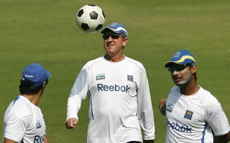 Sri Lankan cricket team coach Bayliss plays with a football as captain Sangakkara warms up in Ahmedabad