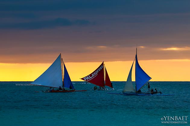 Paraws at sunset off Boracay island.  Despite their simple designs, paraw regattas, or races, are annual events in Boracay and Iloilo City. (Yen Baet)