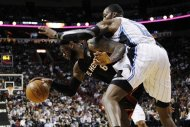 Miami Heat's LeBron James (6) dribbles the ball as Orlando Magic's Dwight Howard (12) defends during the first half of an NBA basketball game, Sunday, March 18, 2012, in Miami. (AP Photo/Lynne Sladky)