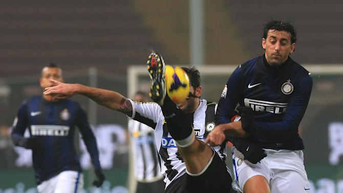 Udinese's Maurizio Domizzi, left, and Inter Milan's Diego Milito challenge for the ball during an Italian Cup soccer match, between Udinese and Inter at the Friuli Stadium in Udine, Italy, Thursday, Jan. 9, 2014