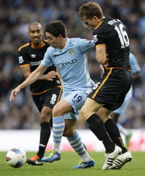 Manchester City's Samir Nasri, center, fights for the ball against Wolverhampton Wanderers' Christophe Berra, right, and Karl Henry during their English Premier League soccer match at The Etihad Stadium, Manchester, England, Saturday Oct. 29, 2011. (AP Photo/Jon Super)