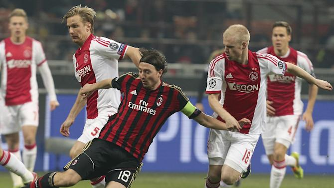 AC Milan midfielder Riccardo Montolivo, center, challenges for the ball with Ajax midfielder Christian Poulsen, left, of Denmark, and Ajax forward Davy Klaassen during a Champions League, Group H, soccer match between AC Milan and Ajax at the San Siro stadium in Milan, Italy, Wednesday, Dec. 11, 2013