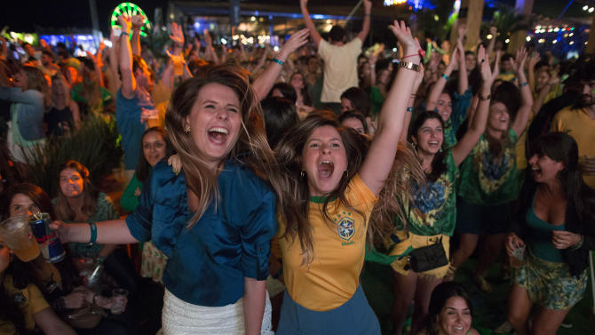 Soccer fans celebrate the second goal scored by Brazil striker Neymar, during a live broadcast at a World Cup viewing party at the Jockey Club, in Rio de Janeiro, Brazil, Thursday, June 12, 2014. After taking the early lead in the opening match of the international soccer tournament, Croatia fell 3-1 to the five-time champion Brazil. (AP Photo/Leo Correa)