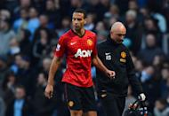 Manchester United's defender Rio Ferdinand (L) is helped from the pitch after being struck by an object thrown from the crowd during a match at The Etihad stadium in Manchester, north-west England on December 9, 2012. A Manchester City fan who confronted Ferdinand on the pitch in an ugly incident following last month's Premier League clash has been banned from attending matches for three years