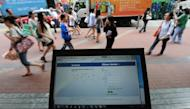 This file photo shows pedestrians walking past a computer displaying login page for the social networking site Facebook, in Hong Kong. HK police said on Sunday they had arrested a 21-year-old man after he reportedly said on Facebook that he would hack several government websites