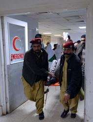 Medics help a victim injured during a rocket attack at Peshawar airport on December 15, 2012. Two rockets landed inside the airport in Peshawar, the main gateway to the semi-autonomous tribal belt on the Afghan border, officials say