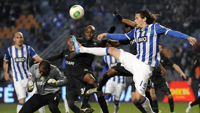 "FC Porto's goalkeeper Helton Arruda, second left, from Brazil, and Luis ""Lica"" Carneiro, right, go for the ball in the last seconds of a Portuguese League soccer match against Academica at the Municipal Stadium in Coimbra, Portugal, Saturday, Nov. 30, 2013. Academica won 1-0 causing Porto's first defeat in the championship"
