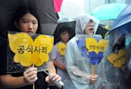 """Supporters of former South Korean """"comfort women"""" who were forced to serve as sex slaves for Japanese troops during World War II hold placards reading, """"official apology,"""" during a weekly protest in front of the Japanese embassy in Seoul on August 15, 2012. Two US lawmakers on Wednesday warned Prime Minister Shinzo Abe not to revise Japan's apology over sexual enslavement in World War II"""