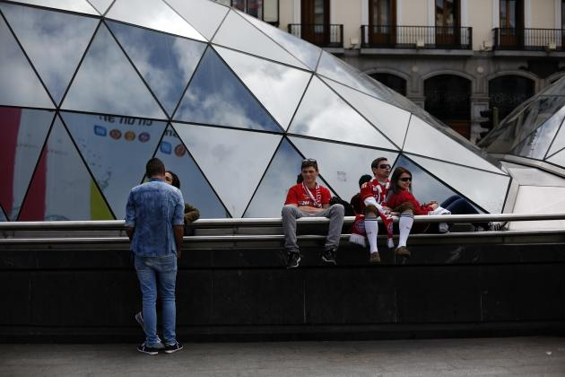 A couple kisses next to Bayern Munich supporters sitting in central Madrid