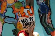 Protesters display placards during a rally in front of the Chinese consular office in Manila on April 11, 2013, against Chinese fishing Philippine waters