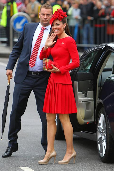 Kate wears a flaming red Alexander McQueen pleated outfit at the The Queen's Diamond Jubilee River Pageant. The Duchess finished her look with a custom hat by Sylvia Fletcher at James Lock & Co. McQue