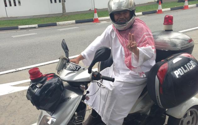 Zeng Guoyan turns up on a 'Police' bike complete in Arabic garb