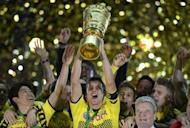 Dortmund's midfielder Sebastian Kehl (C) lifts the trophy next to teammates and German President Joachim Gauck (R) after their German cup final football match against Bayern Munich at the Olympiastadion in Berlin. Dortmund defeated Munich 5-2