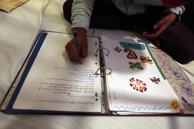 Simona, an 11 year-old Roma schoolgirl who has been living in France for 6 years, does her homework in an hotel in the centre of Nice, southeastern France, November 22, 2013. About fifty migrants from Romania were evicted from an illegal camp on November 27, 2013 where they had been living for 5 months. Six families with school-age children have received emergency housing at an hotel in Nice, as they wait for council housing. The other families have left the encampment with their belongings and will ask for a repatriation grant to Romania. Picture taken November 22, 2013. REUTERS/Eric Gaillard (FRANCE - Tags: POLITICS SOCIETY IMMIGRATION EDUCATION)