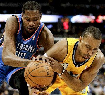 Oklahoma City Thunder's Kevin Durant, left, and Denver Nuggets' Randy Foye, right, fight for a loose ball, resulting in a jump ball, during the fourth quarter of an NBA basketball game Tuesday, Dec. 17, 2013, in Denver. The Thunder won 105-93