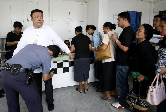 Harry Roque, left, the legal counsel for the massacre of 57 people, including 32 journalists and staff, in Maguindanao province in southern Philippines, is frisked by a jail guard as relatives of the