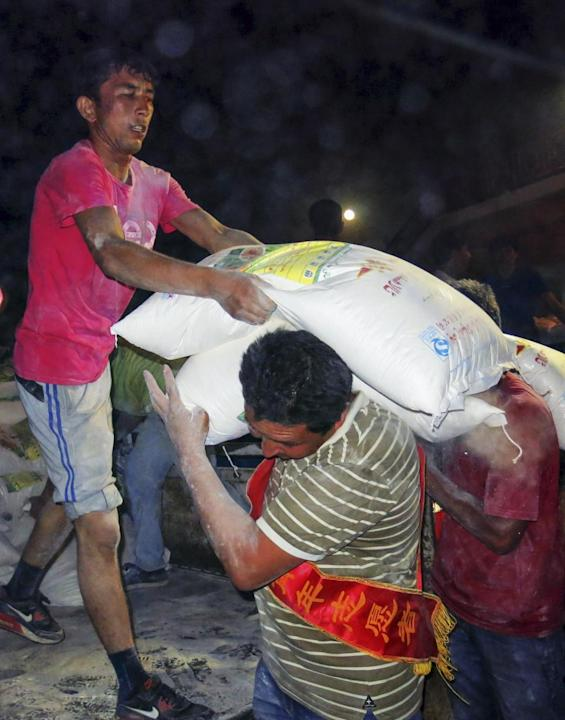 PISHAN, July 4, 2015 (Xinhua) -- Volunteers unload relief materials from a truck in quake-hit Pishan County of Hotan Prefecture, northwest China's Xinjiang Uygur Autonomous Region, July 3, 2015. A