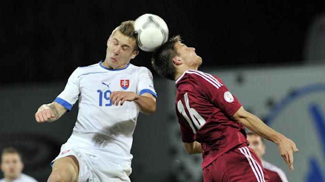 Latvia's Valerijs Sabala, right, vies for the ball with Slovakia's Juraj Kucka during a World Cup 2014 Group G qualification match in Riga, Latvia, on Tuesday. October 15, 2013