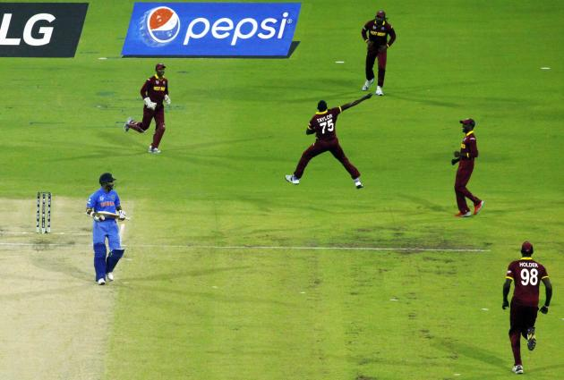 India's batsman Shikhar Dhawan is dismissed as West Indies Chris Gayle and bowler Jerome Taylor react during their Cricket World Cup match in Perth