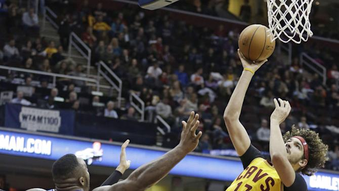 Cleveland Cavaliers' Anderson Varejao (17), from Brazil, shoots to the basket against Orlando Magic's Glen Davis (11) and Orlando Magic' Tobias Harris (12) during the second quarter of an NBA basketball game Thursday, Jan. 2, 2014, in Cleveland. The Cavaliers won 87-81