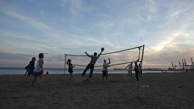 Tourists play volleyball on La Malagueta beach during Dia de Andalucia festivities in Malaga