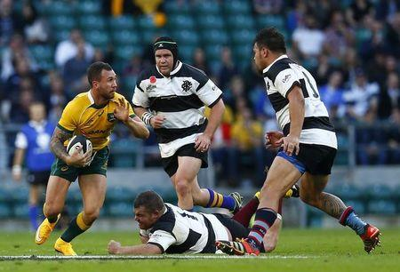 Australia's Quade Cooper is challenged by Barbarians' Matt Stevens and Angus Ta'avao during their international rugby union friendly match at Twickenham