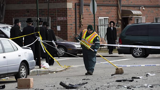 A worker clears debris  from a fatal accident that claimed the lives of two expectant parents, Sunday, March 3, 2013, in the Brooklyn borough of New York. A driver struck the car the couple were riding in early Sunday morning, killing both parents while their baby, who was born prematurely, survived and is in critical condition. (AP Photo/John Minchillo)