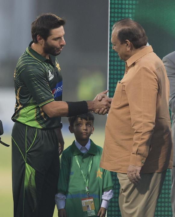 Pakistan's cricket team captain Shahid Afridi, left, shakes hands with President od Pakistan Mamnoon Hussain at the Gaddafi stadium in Lahore, Pakistan, Friday, May 22, 2015. Zimbabwe is the first