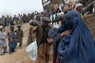 Landslide-affected Afghan villagers receive relief supplies during aid distribution at the scene of the disaster in Argo district of Badakhshan on May 4, 2014