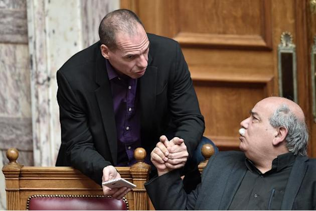 Greek Finance Minister Yanis Varoufakis (L) speaks with the Interior Minister Nikos Voutsis on March 18, 2015 in the parliament in Athens