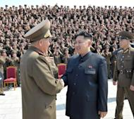 "Undated image provided by the Korean Central News Agency in May shows North Korean leader Kim Jong-Un (C) during a photo session with service members of the KPA Unit 6556. The North said the US arms buildup ""is a prelude to a regional war targeting not only the DPRK (North Korea) but also several Northeast Asian countries..."""