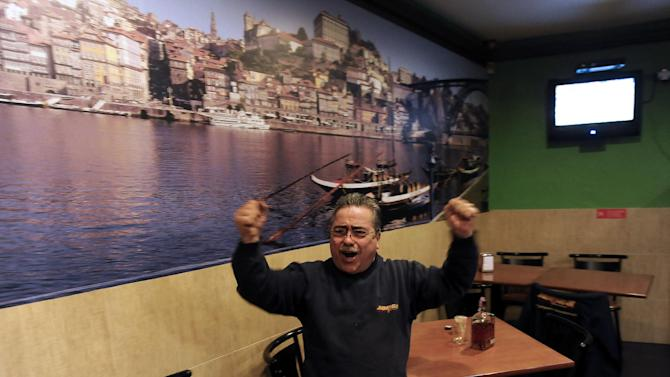 Portuguese Jorge Rodrigues, 58-year-old, celebrates Portugal's Cristiano Ronaldo 3rd goal during the World Cup qualifying playoff second leg soccer match between Sweden and Portugal in his wife coffee-shop, in Porto, Portugal, Tuesday, Nov. 19, 2013. Portugal won 3-2